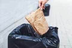 Nahaufnahmehand, die eine zerknitterte Papiertüte im Abfalleimer wirft Stockfotos