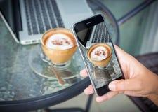 Nahaufnahmehand, die Fotokaffee auf Arbeitstabelle nimmt stockbilder