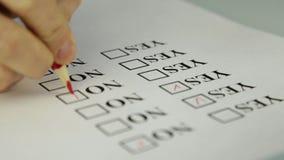 Nahaufnahmehand, die ja füllen und nein am Checklistenkasten mit rotem Bleistift stock footage
