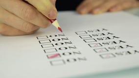 Nahaufnahmehand, die ja füllen und nein am Checklistenkasten mit rotem Bleistift stock video footage
