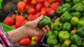 Nahaufnahmehand einer älteren Frau, die grünen Paprika im Supermarkt hält stock footage