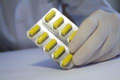 Nahaufnahmehand im medizinischen Gummihandschuh, der herein gelbe Kapseln hält Stockfoto