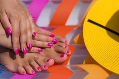 Nahaufnahmehand und -fuß auf einer rosa Luftmatraze im Swimmingpool Stockfotos