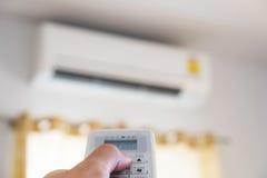 Nahaufnahmehand unter Verwendung der Fernbedienung der Klimaanlage, selektiver Fokus stockfoto