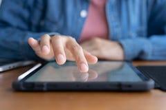 Nahaufnahmehand von asiatischen Frauen benutzen Tablette auf hölzerner Tabelle lizenzfreies stockfoto