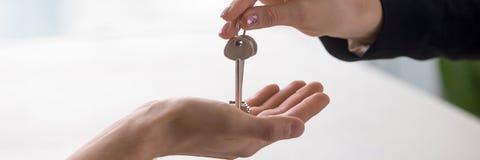 Nahaufnahmehandimmobilienagentur, die dem Hauseigentümer Schlüssel gibt stockbilder