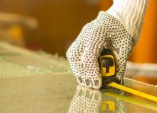 Nahaufnahmehandtragende weiße Arbeitshandschuhe unter Verwendung des Maßwerkzeugs auf transparenter Glasplatte Stockfoto