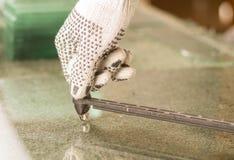 Nahaufnahmehandtragende weiße Arbeitshandschuhe unter Verwendung des metallschneidenden Werkzeugs auf transparenter Glasplatte Lizenzfreies Stockbild