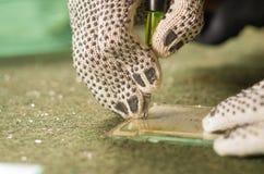 Nahaufnahmehandtragender weißer Arbeitshandschuh unter Verwendung Handausschnitt engravement Werkzeugs für Glas Lizenzfreies Stockfoto