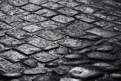 Alte nasse Kopfsteinstraßen-Hintergrundbeschaffenheit Stockfotografie