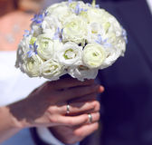 Nahaufnahmehände der Braut und des Bräutigams, die heiratenden weißen Blumenstrauß halten Lizenzfreies Stockbild