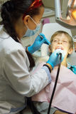 Nahaufnahmejunge, der seins Mund weit während der Inspektion der Mundhöhle durch Zahnarzt öffnet Lizenzfreie Stockbilder