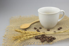 NahaufnahmeKaffeetasse mit Teelöffel auf Juteleinwandtextilisolathintergrund Stockbild