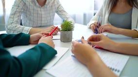 Nahaufnahmekerl- und Studentinhände mit Stiften und Notizbücher auf Tabelle stock footage