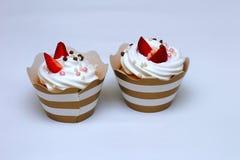 Nahaufnahmekleine kuchen mit gepeitschtem Eisahne verzierten frische Erdbeer- und Schokoladenbälle auf weißem Hintergrund isolat stockfotografie