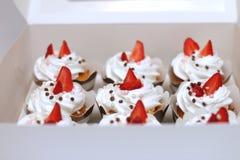 Nahaufnahmekleine kuchen mit gepeitschten Eiern verzierte frische Sahneerdbeer- und Schokoladenbälle im Weißbuchkasten lizenzfreies stockfoto