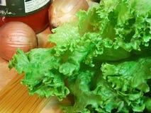 Nahaufnahmekopfsalat und -zwiebeln mit Teigwaren stockfoto
