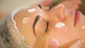 Nahaufnahmekosmetiker verursacht Feuchtigkeitscreme auf dem Gesicht des M?dchens Langsame Bewegung stock video footage