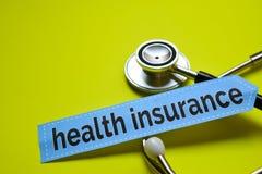 NahaufnahmeKrankenversicherung mit Stethoskopkonzeptinspiration auf gelbem Hintergrund lizenzfreie stockfotos