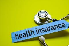NahaufnahmeKrankenversicherung mit Stethoskopkonzeptinspiration auf gelbem Hintergrund stockfotografie