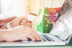 Nahaufnahmekreditkarte, Frau, die online unter Verwendung des Laptops mit der Kreditkarte genießt im Haus kauft Stockfotos