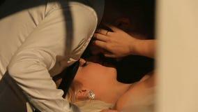 Nahaufnahmekuß der sexy blonden Braut und des hübschen Bräutigams in den Luxusschlafzimmerhotelwohnungen stock video footage