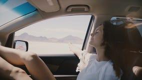 Nahaufnahmelebensstilschuß der glücklichen entspannten Frau im Mitfahrersitz, der entlang Salzseewüste mit dem Fenster offen sich stock video footage