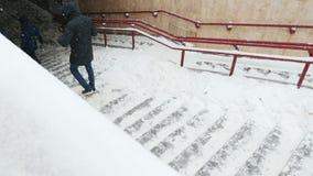 Nahaufnahmeleute gehen unten auf eine schneebedeckte Leiter, Treppenhaus stock footage