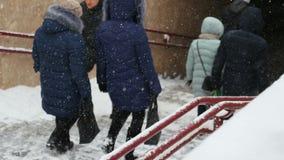 Nahaufnahmeleute gehen unten auf eine schneebedeckte Leiter, Treppenhaus stock video footage