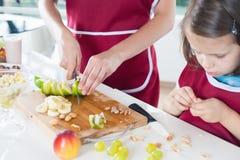 Nahaufnahmemädchen, das mit ihrer Mutter, gesundes Lebensmittel kocht Stockbilder