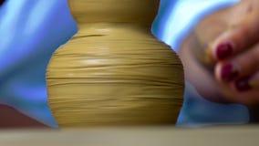 Nahaufnahmemädchen macht prägeartiges Muster auf Lehmvase mit Stock stock video