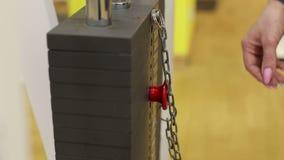 Nahaufnahmemädchen, welches die Stange mit dem Gewicht auf dem Simulator ändert Turnhallenausrüstung stock video footage