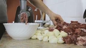 Nahaufnahmemänner ` s übergibt das Hindurchführen des Rindfleisches und des Schweinefleischs und der Zwiebel durch elektrischen F stock footage
