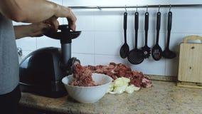 Nahaufnahmemänner ` s übergibt Rindfleisch und Schweinefleisch und Zwiebel durch elektrischen Fleischfleischwolf zu Hause hindurc stock video footage
