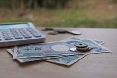 Nahaufnahmemünzenyen und Banknoten Japaner und Taschenrechner Stockbilder