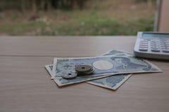 Nahaufnahmemünzenyen und Banknoten Japaner und Taschenrechner Lizenzfreies Stockfoto