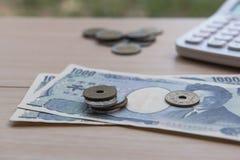 Nahaufnahmemünzenyen und Banknoten Japaner und Taschenrechner auf hölzernem Hintergrund Währung von Japan Lizenzfreies Stockbild