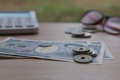 Nahaufnahmemünzenyen und Banknoten Japaner und Taschenrechner auf hölzernem Hintergrund Währung von Japan Stockfotos