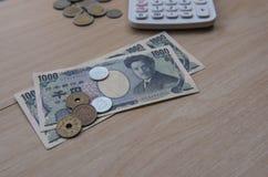 Nahaufnahmemünzenyen und Banknoten Japaner und Taschenrechner auf hölzernem Hintergrund Währung von Japan Lizenzfreies Stockfoto