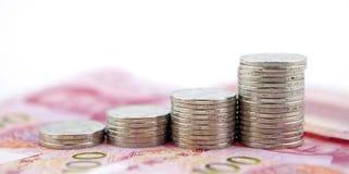 Nahaufnahmemakroansicht bei China Yuan hundert Banknoten und Stapel vier von einem Yuan prägt Stockfotografie