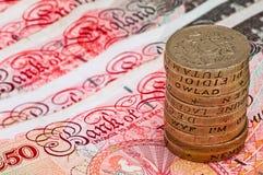 Nahaufnahmemakroansicht an BRITISCHER Währung fünfzig Pfund Banknoten und Stapel ein-Pfund-Münzen Lizenzfreie Stockfotos