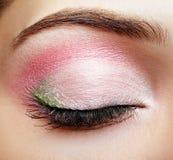 Nahaufnahmemakroschuß des geschlossenen Frauenauges mit rosa und grünem makeu Stockfoto