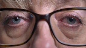 Nahaufnahmemakrotrieb des alten kaukasischen blonden weiblichen Gesichtes in den Gläsern mit ihren Augen, die gerade Kamera betra stock footage