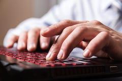 Nahaufnahmemannfinger auf einer Computertastatur Stockbild