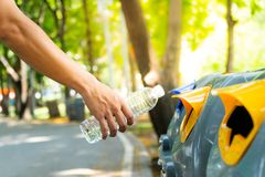 Nahaufnahmemannhand, die leere Plastikwasserflasche in zu rec wirft Stockbilder