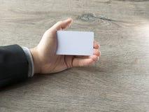 Nahaufnahmemannhand, die Plastikkreditkarte lokalisiert auf dunklem hölzernem Hintergrund hält Lizenzfreie Stockfotografie