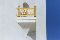 Nahaufnahmemarmorkorridor mit verzierter goldener Schiene von Sheikh Zayed Grand Mosque mit blauem Himmel morgens bei Abu Dhabi,  Lizenzfreies Stockbild