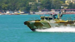 Nahaufnahmemilitärlandegeschwindigkeitsboot mit der Waffen Flößen schnell auf der blauen Oberfläche von Meer Spuren des Schaums h stock footage