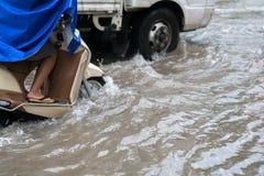 Nahaufnahmemotorradfahrer reitet entlang eine überschwemmte Straße in Hanoi-Stadt, Vietnam Lizenzfreies Stockfoto