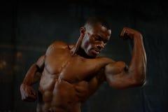 Nahaufnahmemuskeln des hübschen Bodybuilders des Afroamerikaners, der mit dem nackten Torso auf dem schwarzen Studiohintergrund a lizenzfreie stockfotografie